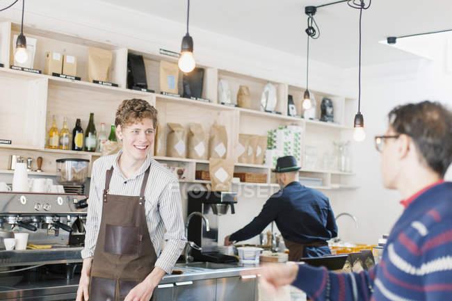 Happy barista talking to customer — Stock Photo