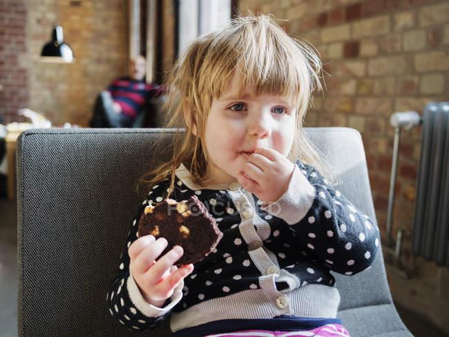 Маленькая девочка ест пирожное — стоковое фото