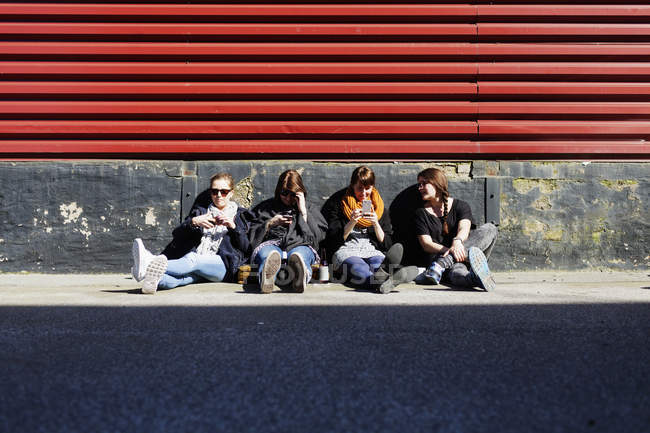 Друзья с помощью смартфонов на улице — стоковое фото