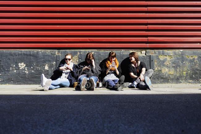 Friends using smart phones on street — Stock Photo