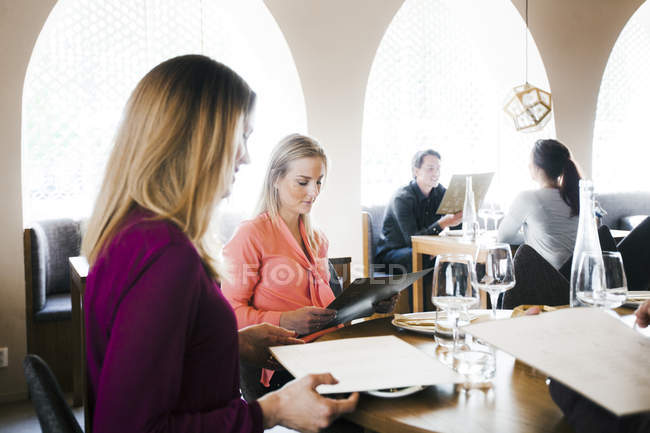 People reading menu while sitting at table — Stock Photo
