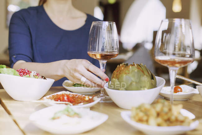Woman holding wineglass at table — Stock Photo