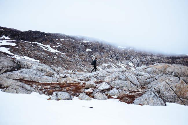 Hombre caminando en el paisaje cubierto de nieve - foto de stock
