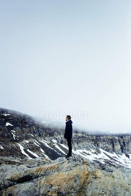 Hombre de pie en el paisaje cubierto de nieve - foto de stock