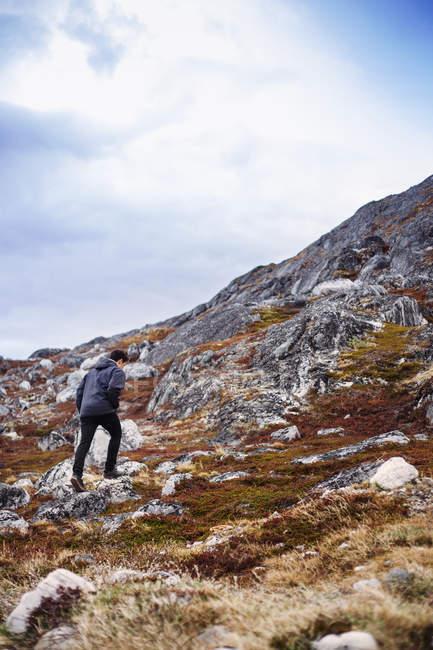 Hombre caminando sobre un paisaje rocoso - foto de stock