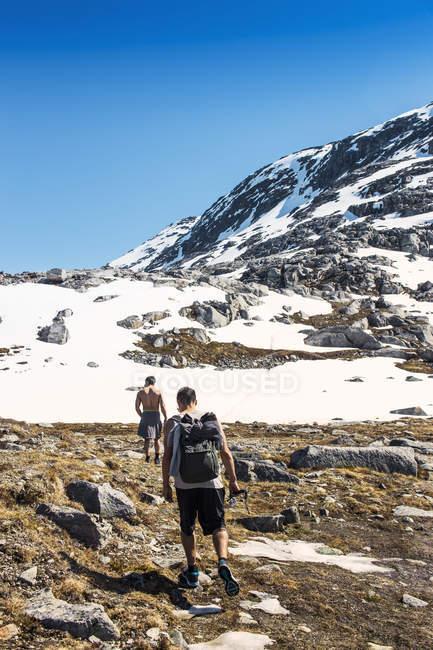 Excursionistas a pie de las montañas rocosas - foto de stock