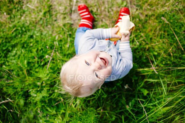 Happy boy sitting on grassy field — Stock Photo