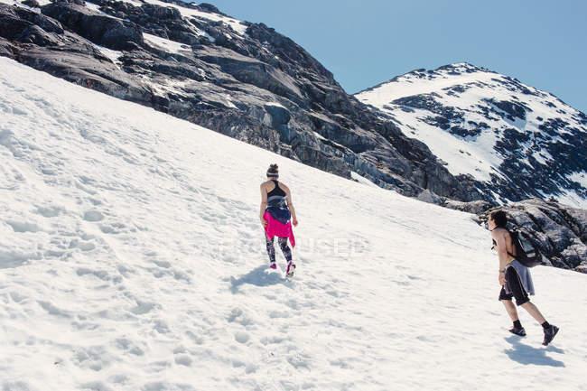 Excursionistas a pie sobre la nieve cubrieron las montañas - foto de stock