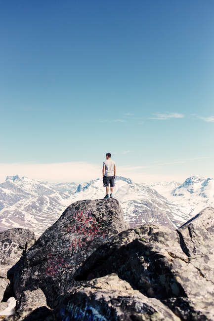 Hombre de pie en la cima de la montaña - foto de stock