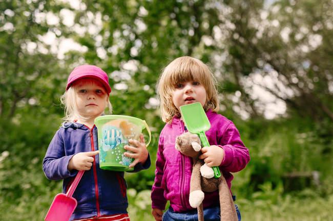 Дівчата з іграшками, садові — стокове фото