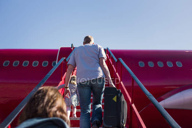 People walking on staircase towards airplane — Stock Photo