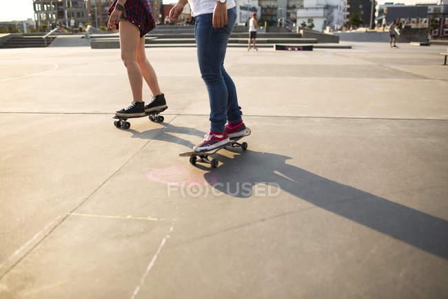 Female skateboarders riding in skate park — Stock Photo