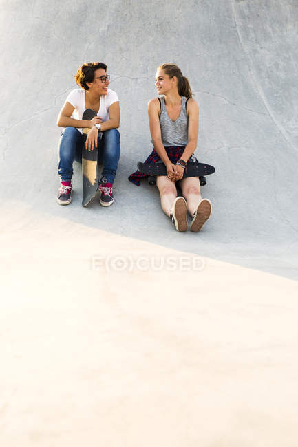 Friends with skateboards sitting at skate park — Stock Photo