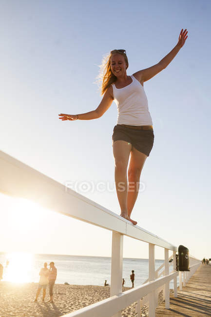 Young woman walking on bridge rail — Stock Photo