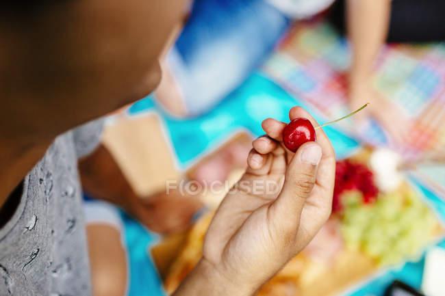 Man holding cherry at park — Stock Photo