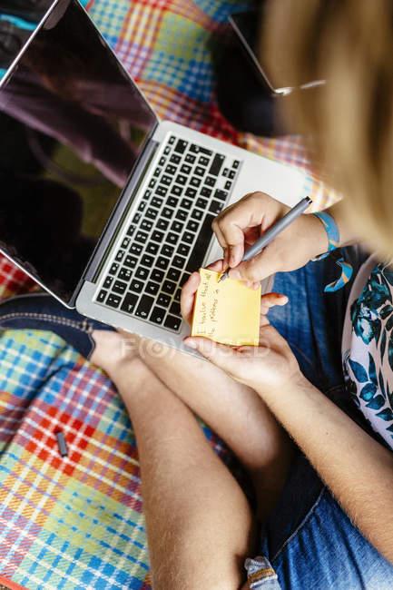 Студент пишет на клейкой ноте — стоковое фото