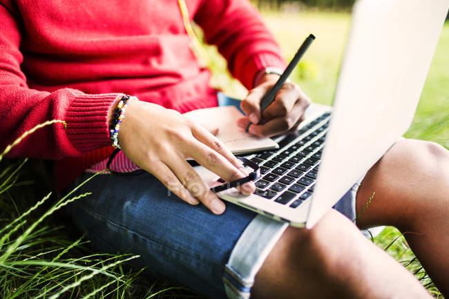 Mann schreibt Notizen und hält Laptop in der Hand — Stockfoto