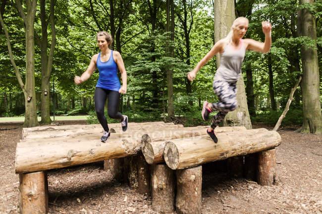 Women running over logs — Stock Photo
