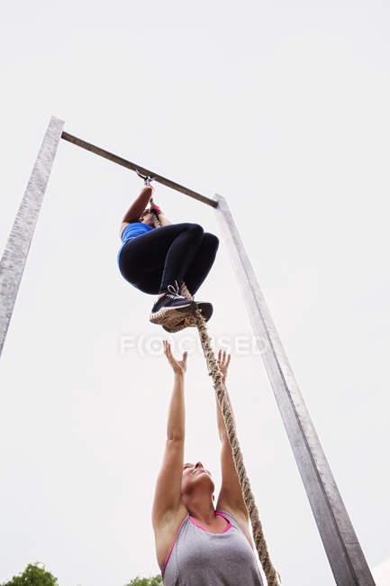 Fit woman climbing rope — Stock Photo