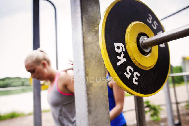 Woman helping friend in lifting barbell — Stock Photo