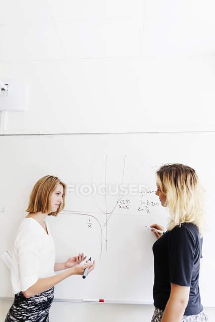 Студенты вузов обсуждают это на доске — стоковое фото