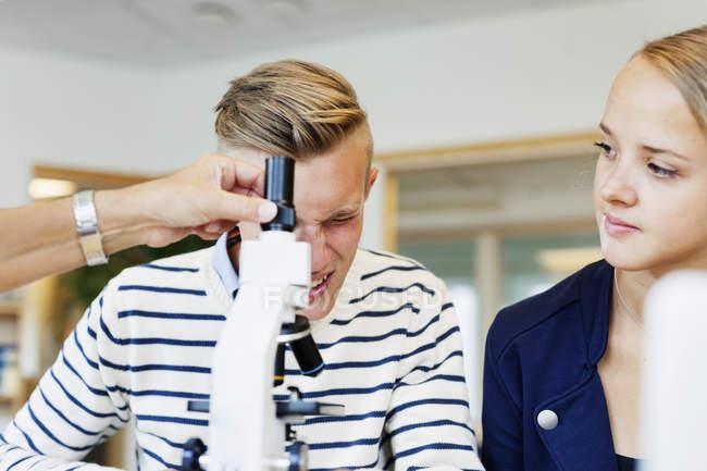 Студент ВУЗу, використовуючи мікроскоп — стокове фото