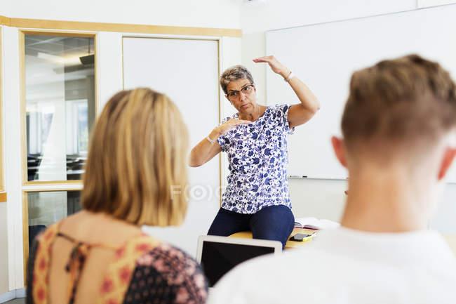 Profesor explicando a los estudiantes en el aula - foto de stock