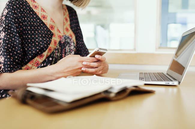 Studente femminile utilizzando il telefono cellulare — Foto stock