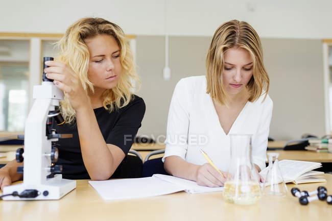Étudiant à l'aide du microscope et camarade de classe d'écriture — Photo de stock