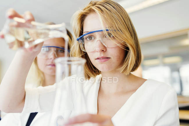 Female students performing science experiment — Stock Photo