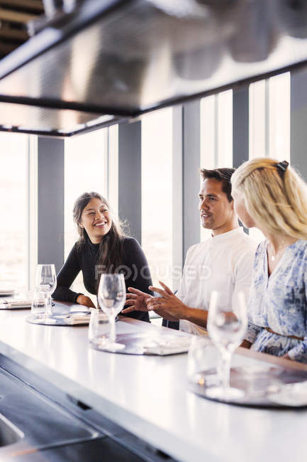 Man with female friends having conversation — Stock Photo
