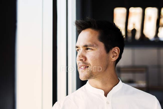 Un hombre reflexivo mirando por la ventana - foto de stock