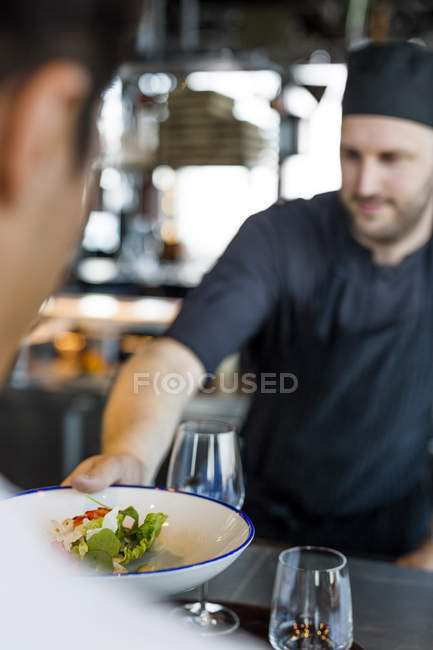 Chef serving dish to customer — Stock Photo