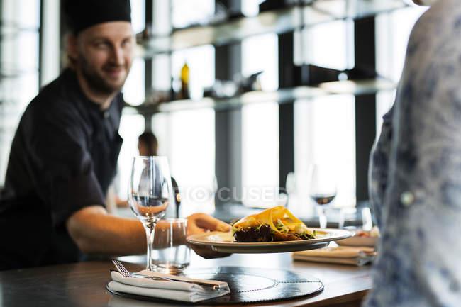 Chef serving dish to customer — Stock Photo
