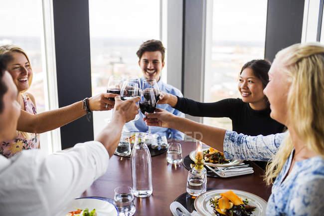 Amigos brindando con vino tinto - foto de stock