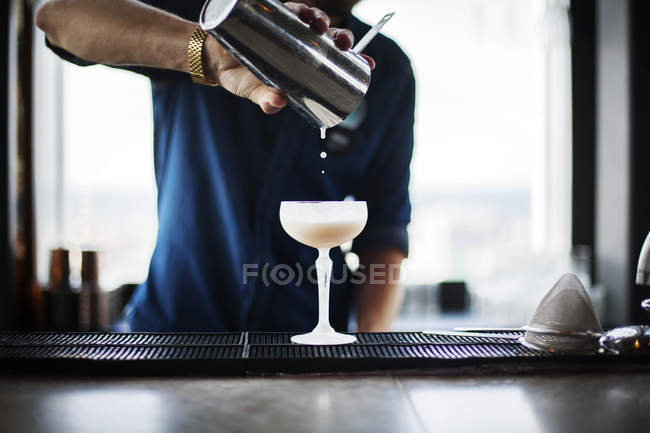 Bartender pouring cocktail in glass — Stock Photo