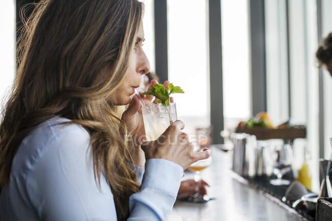 Junge Frau nippen cocktail — Stockfoto
