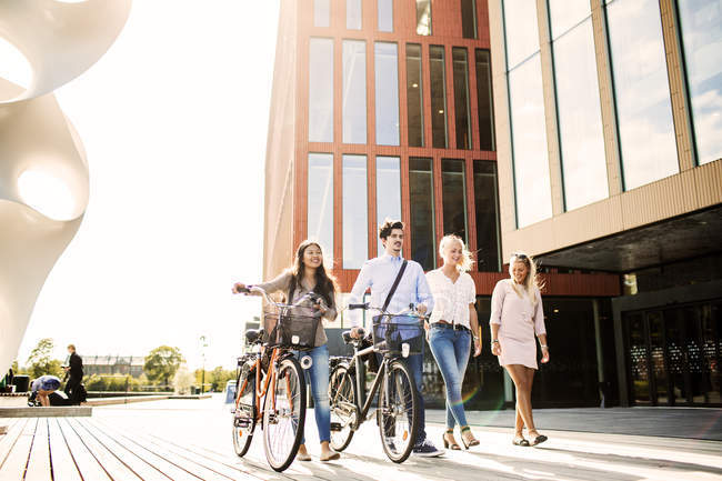 Young friends with bicycles walking — Stock Photo