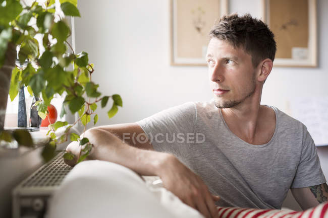 Young adult man sitting on sofa — Stock Photo