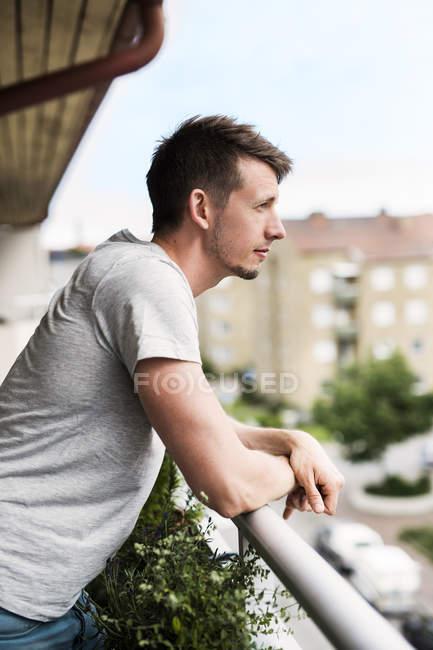 Portrait of man leaning on balcony — Stock Photo