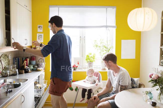 Pareja gay con bebé chica en cocina - foto de stock