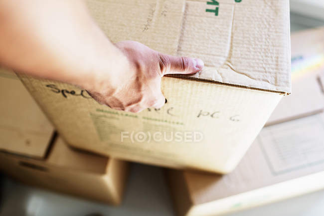 Man picking up cardboard box — Stock Photo