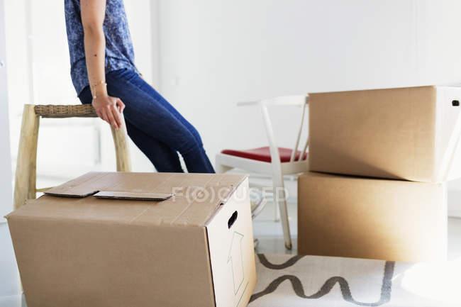 Frau im neuen Zuhause in der Nähe von Boxen — Stockfoto