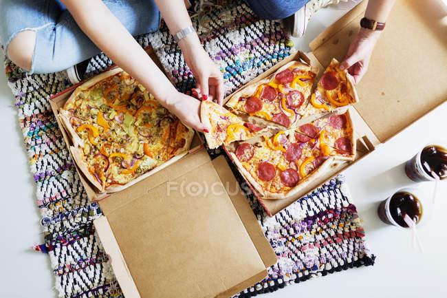 Друзья едят пиццу в новом доме — стоковое фото