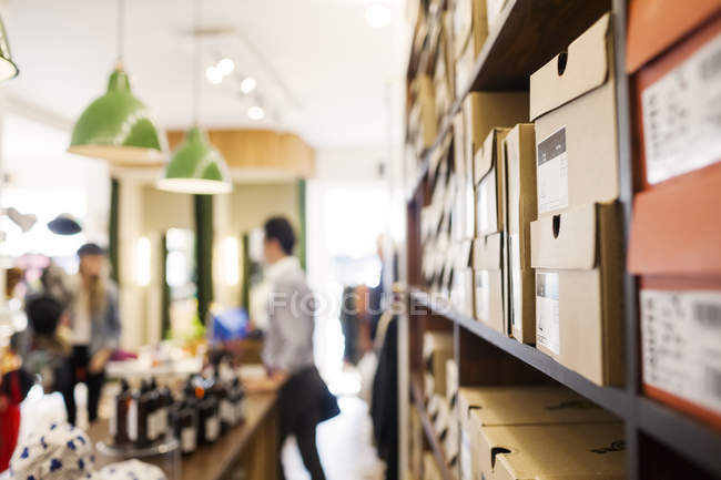 Boxes on shelves and people — Stock Photo