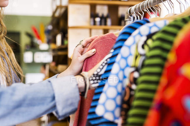 Woman choosing clothes in store — Stock Photo