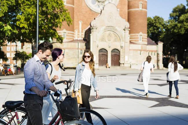 Друзья с велосипедами ходят по улице — стоковое фото