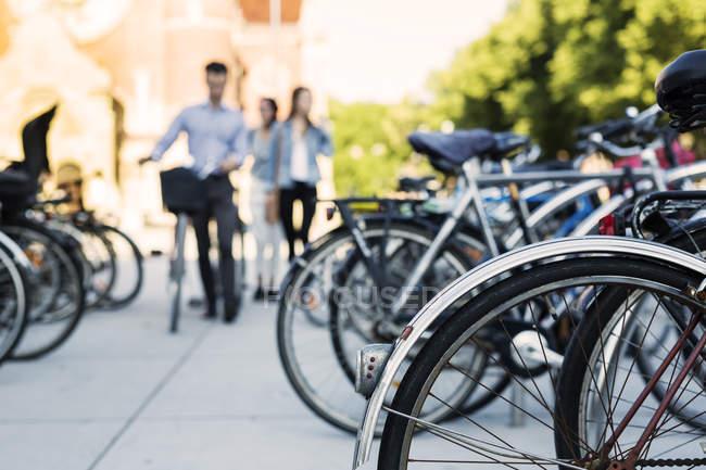 Amigos con bicicletas caminando por la calle - foto de stock