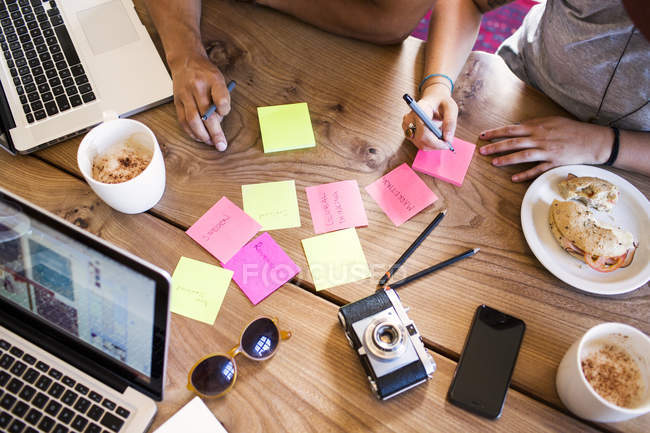 Friends writing on adhesive notes — Stock Photo