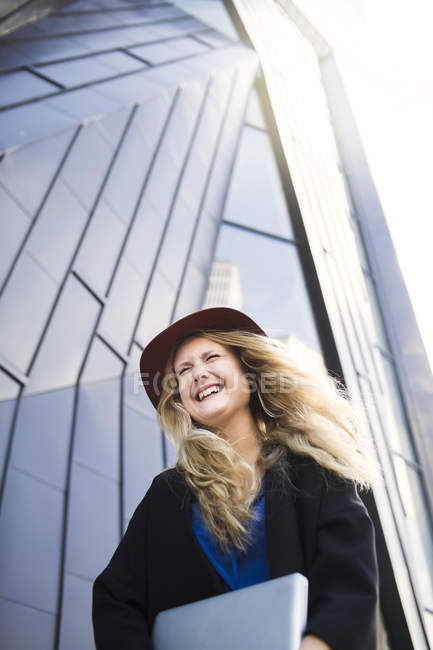 Happy woman in hat against building — Stock Photo